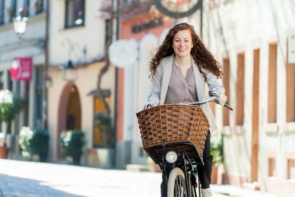 SPD-Bundestagskandidatin Julia Söhne auf dem Fahrrad in der Innenstadt von Freiburg.